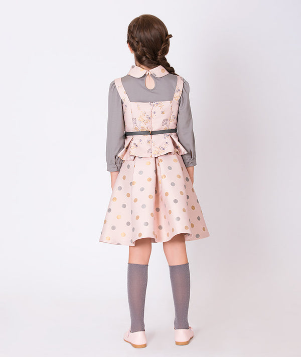 Back of girl in gray blouse with pink collar, pink vest and polka dot pink skirt for kids