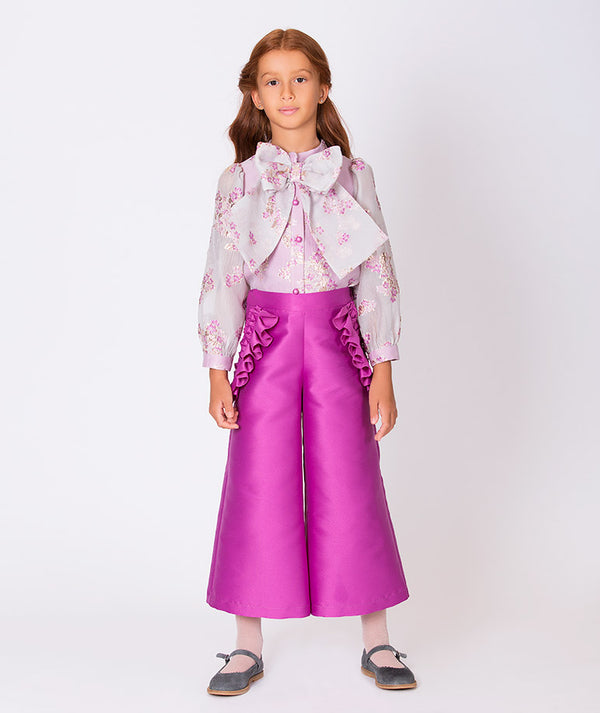 Girl in sheer blouse with magenta flower embroidery and magenta party pants for kids