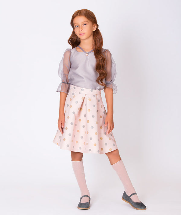 Girl in sheer gray blouse and long pink pleated skirt with gray and orange polka dots for kids by Mama Luma