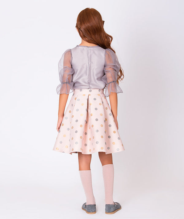 Back of girl in sheer gray blouse and long pink pleated skirt with gray and orange polka dots for kids by Mama Luma