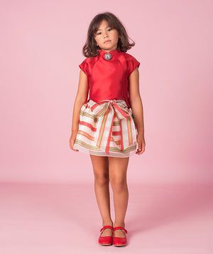 Girl in designer kids outfit with red blouse and striped skirt for kids