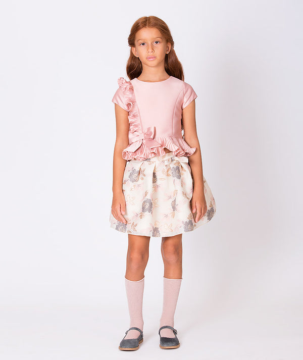 Girl in ruffle pink blouse and beige flower print skirt for kids