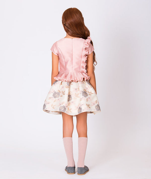Back of girl in ruffle pink blouse and beige flower print skirt for kids