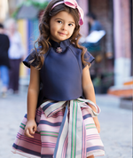 Baby clothes design with smiling girl in navy blue taffeta blouse with embellished button and pink blue and teal striped chiffon flared skirt with bow