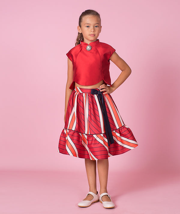 Girl in red blouse and striped skirt with blue bow by Mama Luma