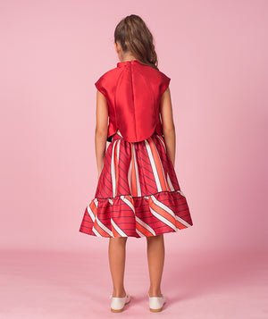 Back of girl in designer red blouse and striped skirt for kids