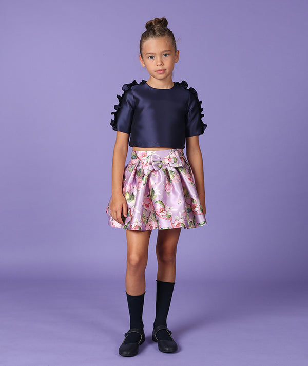Girl in designer kids outfit, blue blouse and flower print skirt