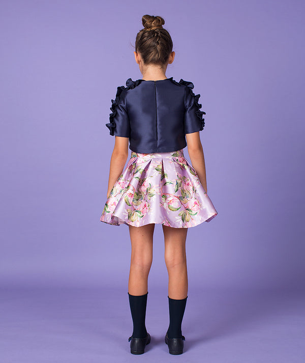 Back of girl in chic navy blue blouse and floral skirt for kids