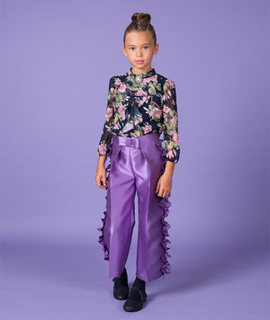 girl in chic floral blouse and purple ruffle pants