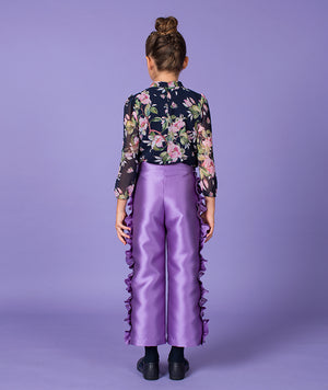 Back of girl in chic floral blouse and purple ruffle pants