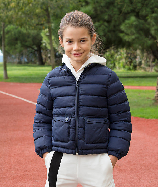 Girl in navy blue puffy jacket for kids and white athleisure pants