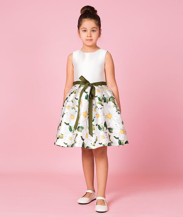 Girl in daisy print dress with bow by Mama Luma