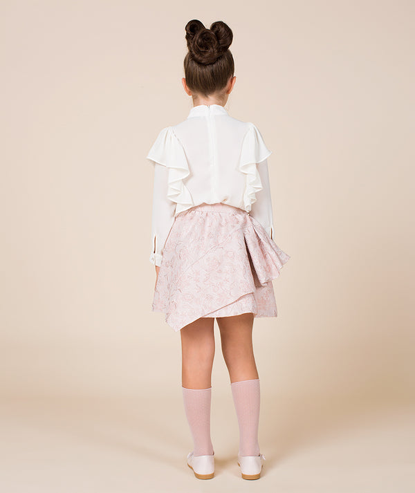 Kid in ruffle white top, pink skirt, pink socks and pink shoes for girls