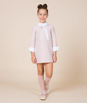 Girl in pink daisy print dress with bow and collar by Mama Luma