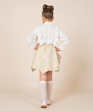 Back of girl in luxury outfit with white blouse and beige jacquard skirt for kids by Mama Luma