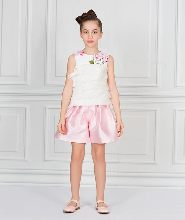 Girl in white blouse with flower appliques and pink taffeta shorts for kids