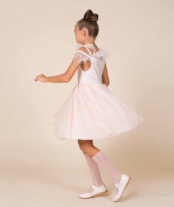 Girl twirling in Mama Luma dress with pink tulle skirt
