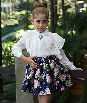 Girl in special occasion outfit featuring white chic blouse for kids and navy blue flower print skirt by Mama Luma