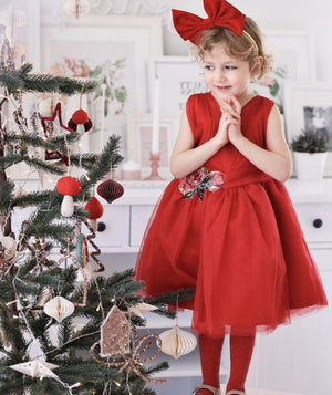 Girl in red Christmas dress next to tree by Mama Luma
