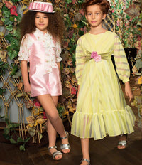 Girl in yellow sheer and chiffon full length party dress  with rose bouquet applique on waist and girl in pink jumper with chiffon tulip blouse for kids