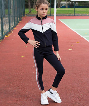 Girl in athleisure tracksuit for kids by Mama Luma posing on a tennis court