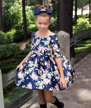 Girl in a park wearing a navy blue flower print flared party dress for kids by Mama Luma