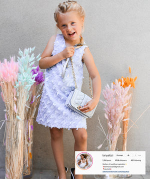 Tanya Lozi's daughter in a blue sequin dress for kids with a designer bag