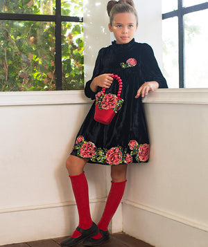 Girl in corner of a room with black velvet dress with roses for kids by Mama Luma