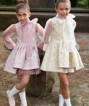 Girl in beige designer dress with big bow and girl in pink jacquard special occasion dress for kids