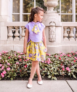 Angel Hou's daughter wearing a lilac blouse with a yellow flower print tie and blouse for kids by Mama Luma