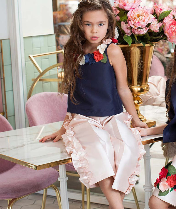 Girl in navy blouse with flower appliques and pink ruffle pants for kids