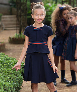 Girl in navy blue designer outfit with blouse and pleated skirt for kids, with two girls in Mama Luma dresses whispering secrets to each other