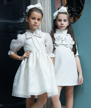 Two girls: one in cream jacquard dress for girls with sheer skirt and bow on neck, the other in white dress with flower appliques and headbands for kids