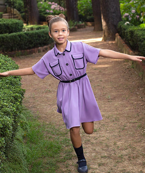 Girl in a park wearing a purple Mama Luma dress for kids