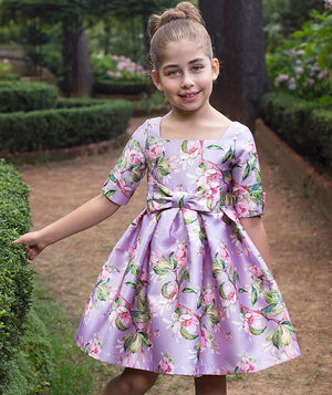 Girl in park with lilac flower print dress with bow by Mama Luma