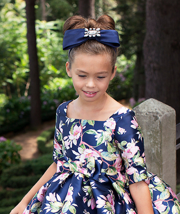 Girl in floral print designer dress and headband by Mama Luma