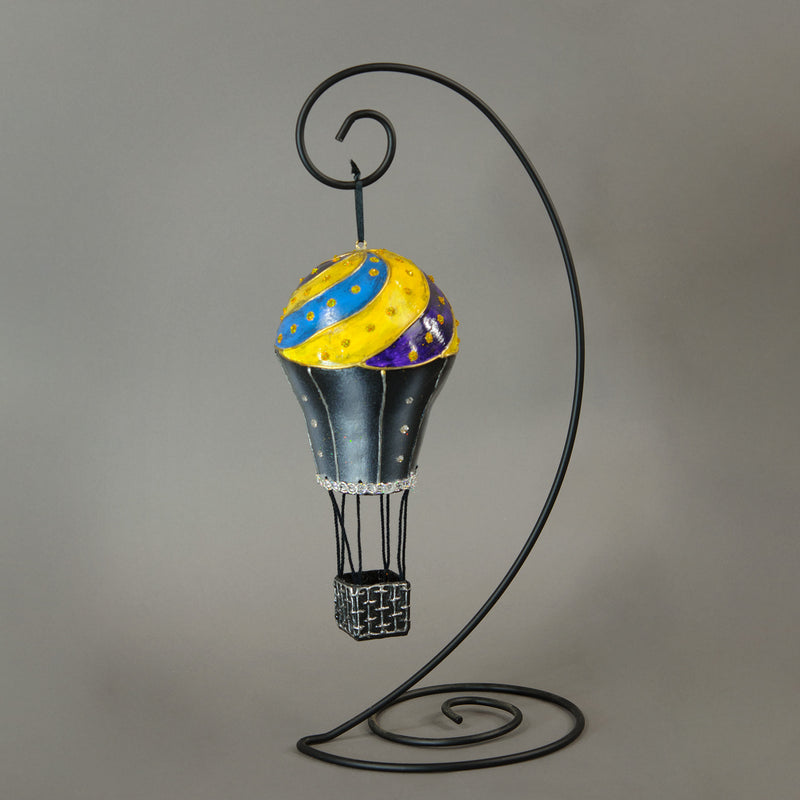 "This hot air balloon ornament is perfect for any whimsical display for Christmas or year round. Beautiful in hanging displays either alone or in a fantasy multiple ornament display. Handmade paper-mache balloon ornament in a black, yellow, blue and purple swirl motif. Accented with metal findings, Swarovski crystals and fine iridescent glitter. Measures about 5"" tall and 2.5"" wide. Great for holiday or year-round display."