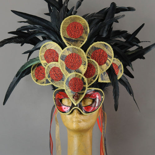 Become a Goddess at your next masquerade party in this stunning Red, black and gold Fire Sylph Masquerade Mask! This is an avant-garde piece with a crest of hand made paper panels in a peacock motif laying over pitch black coque feathers. Embellished with Swarovski crystals, and polished stones.  Handmade in the USA using traditional Venetian paper-mache technique. Lined with hypoallergenic stretch velvet for comfort. Detail view.