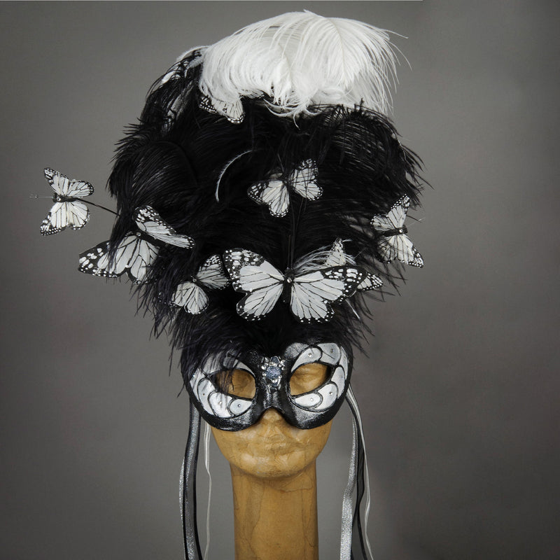 Beautiful Masquerade Mask, crested in Black and White Ostrich Plumes and assorted plumage. White feather monarch butterflies flutter on the crest. Embellished with Swarovski crystals, dichroic glass and polished black quartz.  Hand made in the USA using traditional Venetian paper-mache technique. Lined with hypoallergenic stretch velvet for comfort.