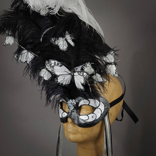 Beautiful Masquerade Mask, crested in Black and White Ostrich Plumes and assorted plumage. White feather monarch butterflies flutter on the crest. Embellished with Swarovski crystals, dichroic glass and polished black quartz.  Hand made in the USA using traditional Venetian paper-mache technique. Lined with hypoallergenic stretch velvet for comfort. Side view.