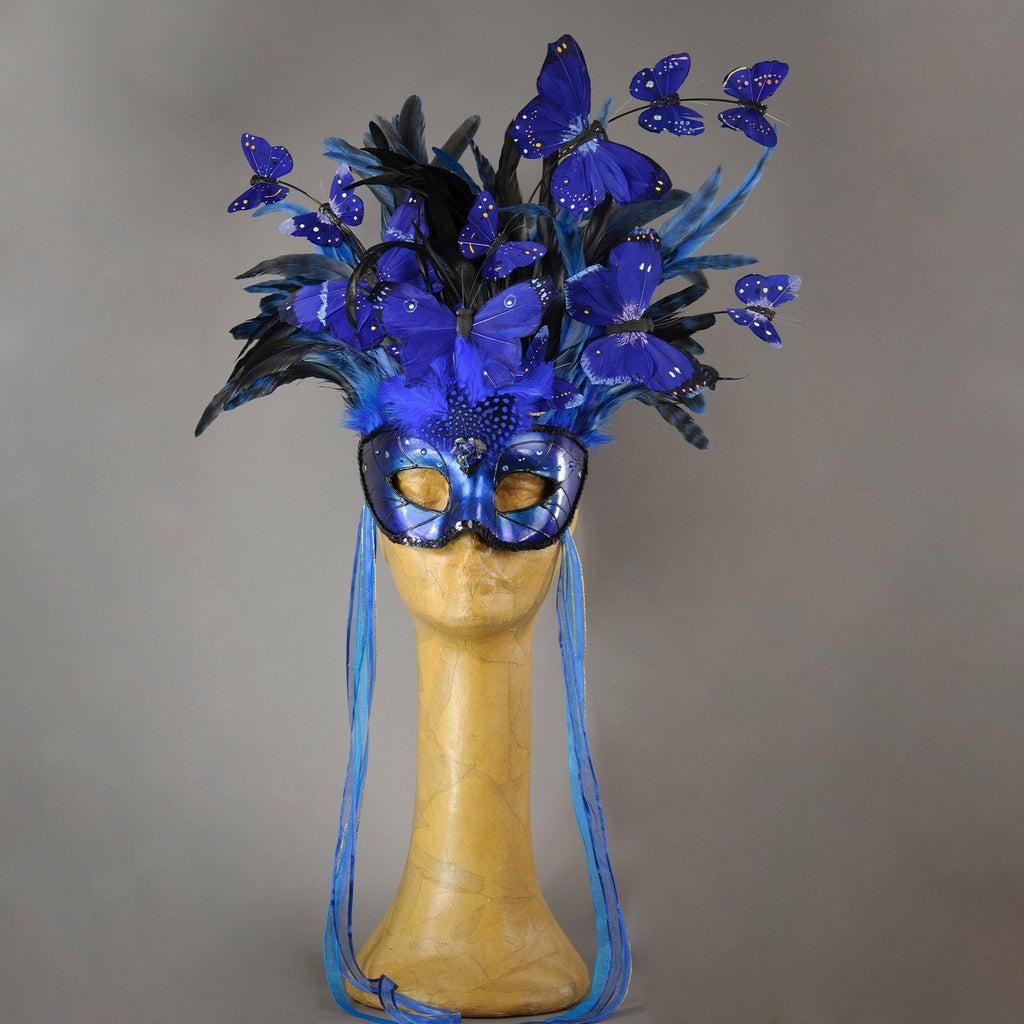 Beautiful Masquerade Mask, in shades of black and Metallic blue.Crested with black coque feathers and assorted dyed plumage. Blue feather morpho butterflies flutter on the crest. Embellished with Swarovski crystals, dichroic glass and polished Lapis stones.  Hand made in the USA using traditional Venetian paper-mache technique. Lined with hypoallergenic stretch velvet for comfort.