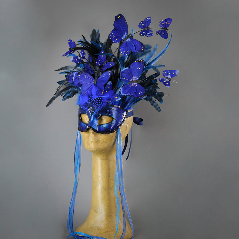 Beautiful Masquerade Mask, in shades of black and Metallic blue.Crested with black coque feathers and assorted dyed plumage. Blue feather morpho butterflies flutter on the crest. Embellished with Swarovski crystals, dichroic glass and polished Lapis stones.  Hand made in the USA using traditional Venetian paper-mache technique. Lined with hypoallergenic stretch velvet for comfort. Side view.