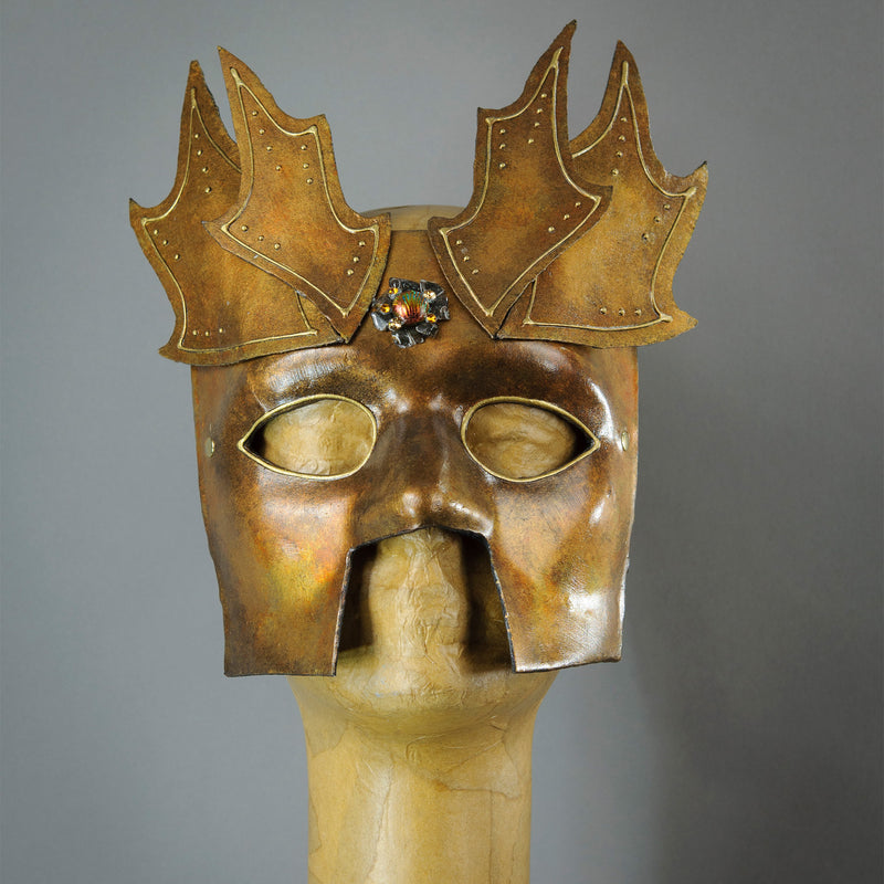 The Copper Warrior Bauta Masquerade mask is Inspired by medieval armor of the Renaissance. With it's masculine lines, this mask is particularly popular for men and is a lightweight and comfortable mask that is perfect for Halloween and Masquerade events. Mask is treated in shades of gold and copper with Dragon Wing panel armor, metal findings and assorted polished gems.  Handmade in the USA using traditional Venetian paper-mache techniques. Lined with hypoallergenic stretch velvet for comfort.