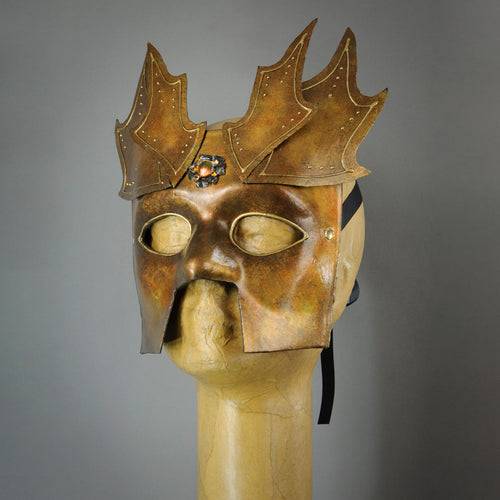 The Copper Warrior Bauta Masquerade mask is Inspired by medieval armor of the Renaissance. With it's masculine lines, this mask is particularly popular for men and is a lightweight and comfortable mask that is perfect for Halloween and Masquerade events. Mask is treated in shades of gold and copper with Dragon Wing panel armor, metal findings and assorted polished gems.  Handmade in the USA using traditional Venetian paper-mache techniques. Lined with hypoallergenic stretch velvet for comfort. Side view.