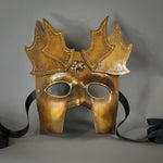 The Copper Warrior Bauta Masquerade mask is Inspired by medieval armor of the Renaissance. With it's masculine lines, this mask is particularly popular for men and is a lightweight and comfortable mask that is perfect for Halloween and Masquerade events. Mask is treated in shades of gold and copper with Dragon Wing panel armor, metal findings and assorted polished gems.  Handmade in the USA using traditional Venetian paper-mache techniques. Lined with hypoallergenic stretch velvet for comfort. Detail view.
