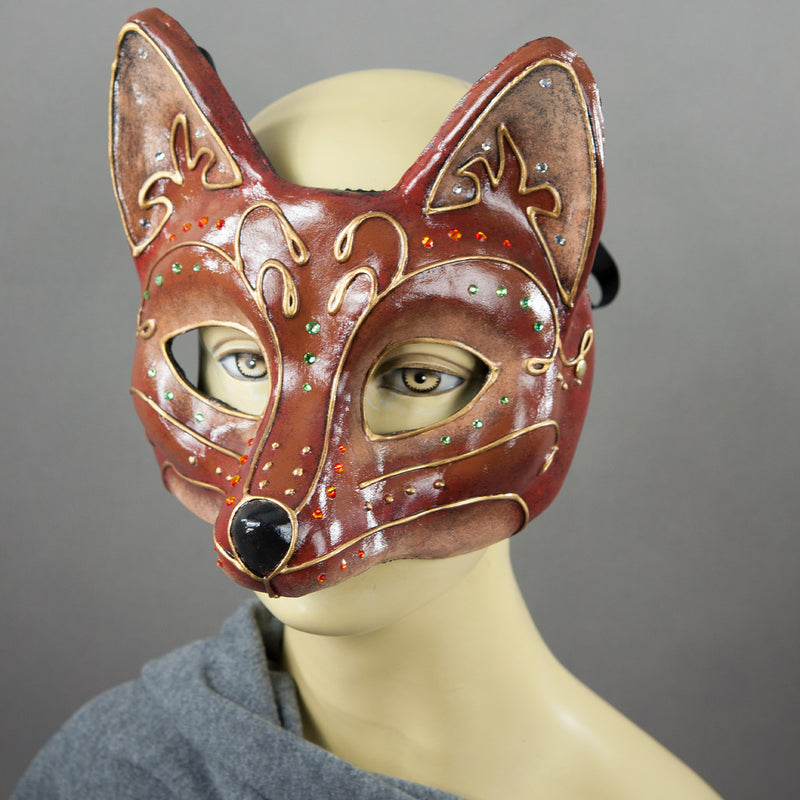 Fancy Red Fox Mask detail. A lightweight comfortable mask inspired by the sly red fox, decorated with an elegant gold scroll motif and embellished with Swarovski Crystals and assorted gems.  Hand Made in the USA using traditional Venetian paper-mache techniques and lined with soft stretch velvet for comfort.