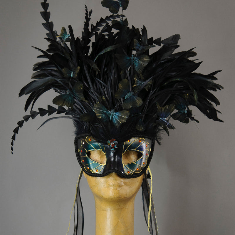 Beautiful Masquerade Mask, in iridescent shades over black. Crested with black coque feathers. Iridescent black feather butterflies flutter on the crest. Embellished with Swarovski crystals, and polished gemstones.  Hand made in the USA using traditional Venetian paper-mache technique. Lined with hypoallergenic stretch velvet for comfort. Detail.