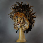 Stunning Lion Mask with a luxe crest of natural coque and assorted pheasant plumage. Embellished with Swarovski crystals, and assorted polished gem stones. Sure to turn heads at any costume, masquerade or Halloween party!  Hand-made in the USA using traditional Venetian paper-mache technique. Lined with hypoallergenic stretch velvet for comfort. Side view.