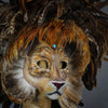 Stunning Lion Mask with a luxe crest of natural coque and assorted pheasant plumage. Embellished with Swarovski crystals, and assorted polished gem stones. Sure to turn heads at any costume, masquerade or Halloween party!  Hand-made in the USA using traditional Venetian paper-mache technique. Lined with hypoallergenic stretch velvet for comfort. Detail side view.