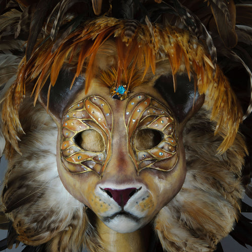 Stunning Lion Mask with a luxe crest of natural coque and assorted pheasant plumage. Embellished with Swarovski crystals, and assorted polished gem stones. Sure to turn heads at any costume, masquerade or Halloween party!  Hand-made in the USA using traditional Venetian paper-mache technique. Lined with hypoallergenic stretch velvet for comfort. Detail view.